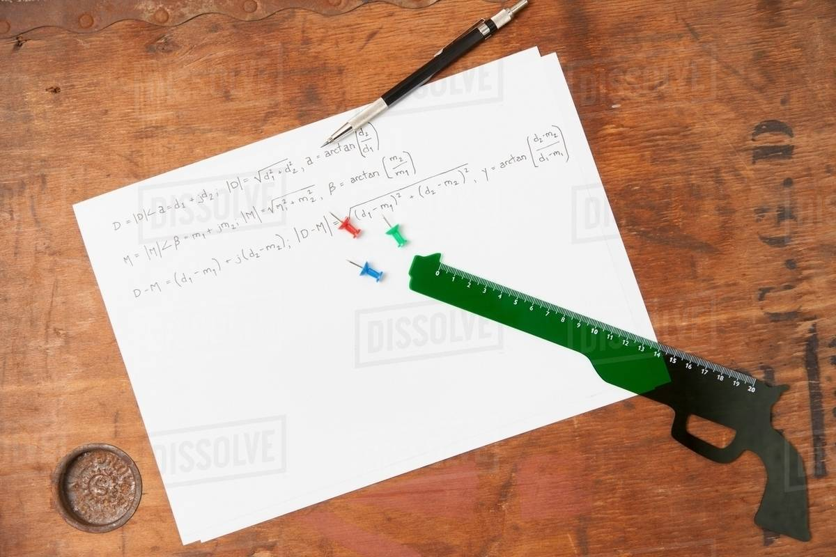 Gun shaped ruler and pen on paper stock photo