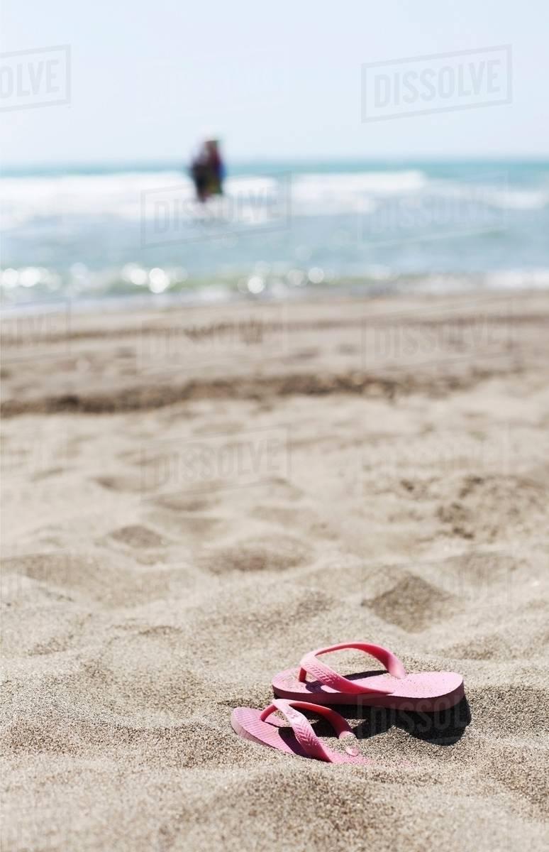 3fed6bbf1 Flip flops on sandy beach - Stock Photo - Dissolve
