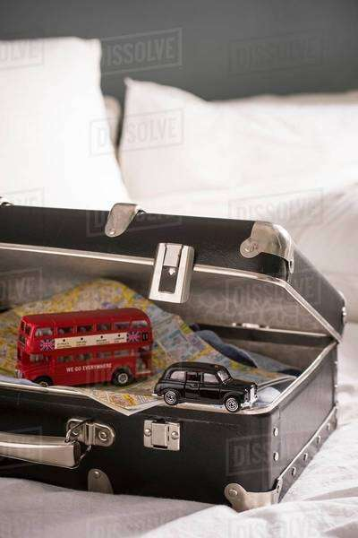 Open suitcase on bed with toy London bus and black cab Royalty-free stock photo