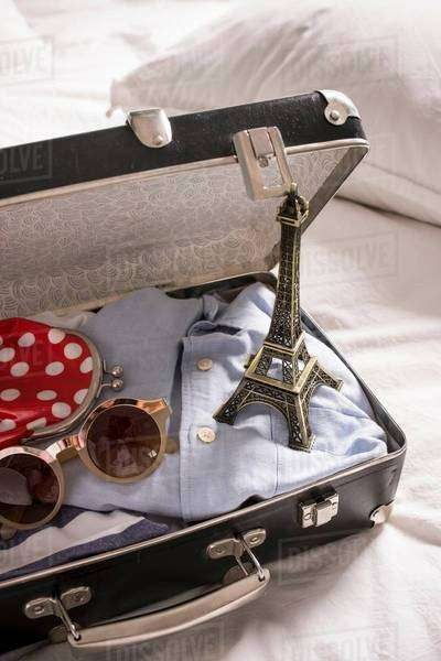 Open suitcase on bed with eiffel tower souvenir and sunglasses Royalty-free stock photo