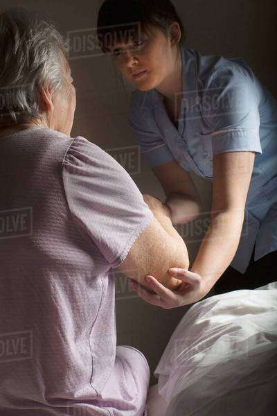 Personal care assistant helping senior woman to get up Royalty-free stock photo