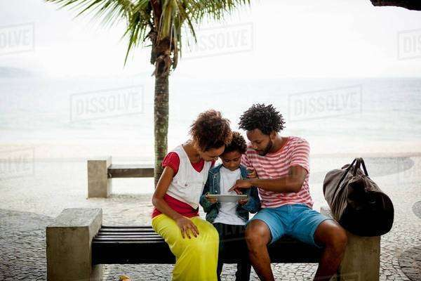 Couple and son sitting on park bench using digital tablet, Ipanema beach, Rio De Janeiro, Brazil Royalty-free stock photo