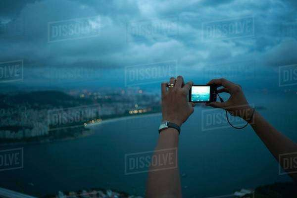 Close up of female hands photographing view of Rio De Janeiro at night, Brazil Royalty-free stock photo