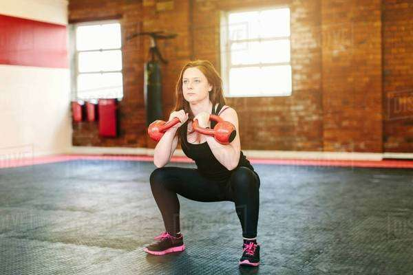 Woman squatting lifting kettlebells Royalty-free stock photo