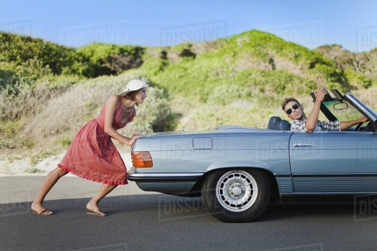 woman pushing car as boyfriend steers stock photo dissolve