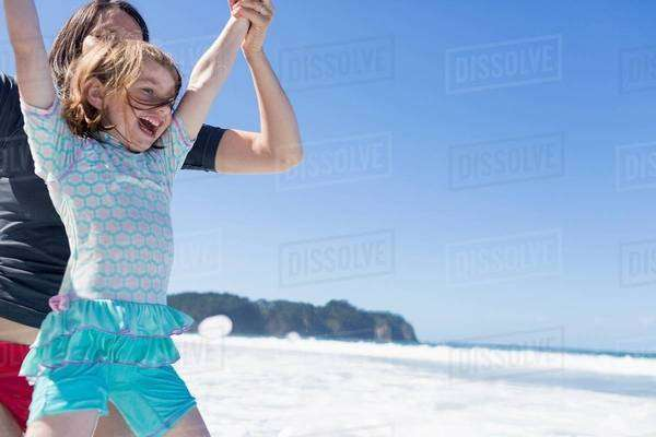 Mother and daughter jumping in sea, Hot Water Beach, Bay of Islands, New Zealand Royalty-free stock photo