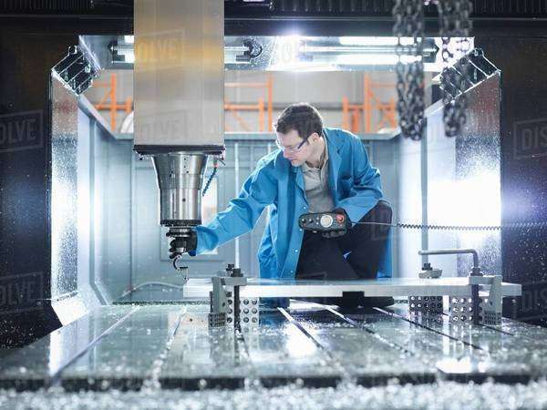 Worker in large CNC machine in plastics factory Royalty-free stock photo