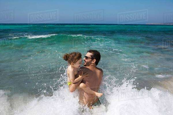 Father and daughter playing in waves Royalty-free stock photo