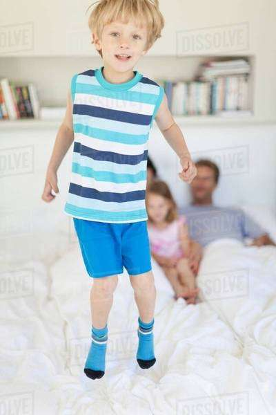 Boy jumping on parents' bed Royalty-free stock photo
