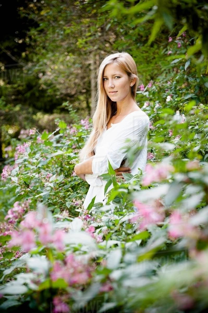 Woman Standing In Flower Bushes Stock Photo Dissolve