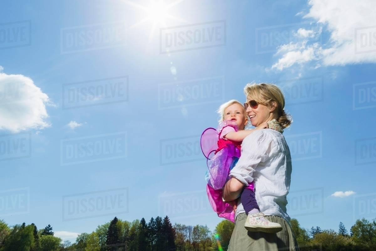Mother carrying toddler girl outdoors Royalty-free stock photo
