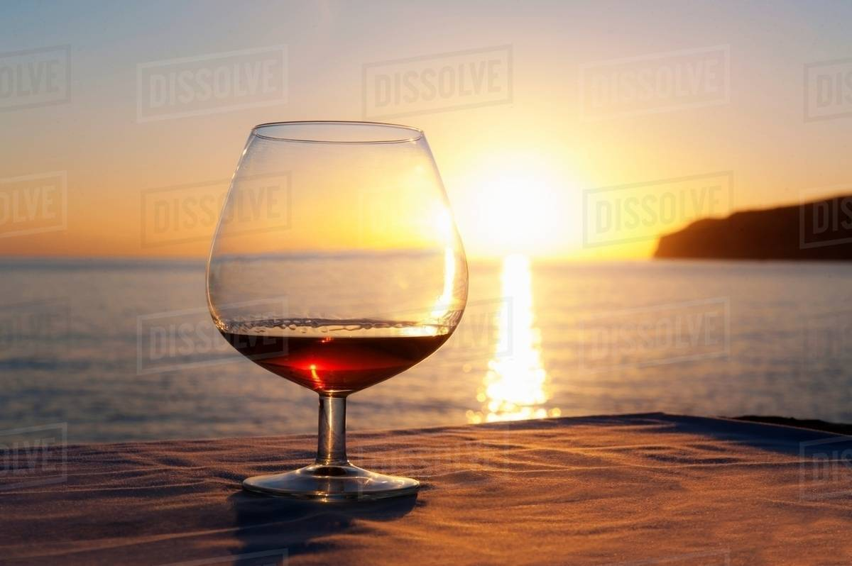 Sunset over sea with brandy glass on table, Mallorca, Spain stock photo