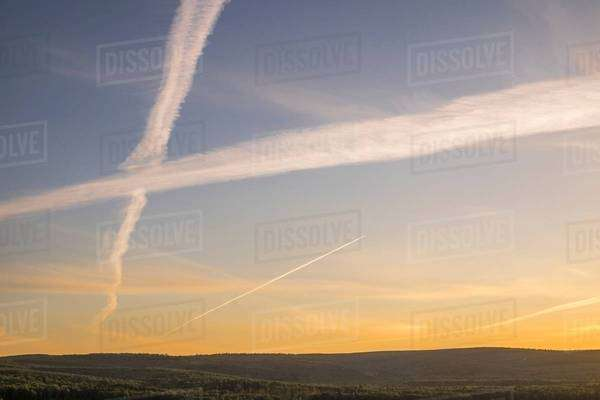 Silhouetted hillside view of sunset sky with criss crossing vapour trails Royalty-free stock photo