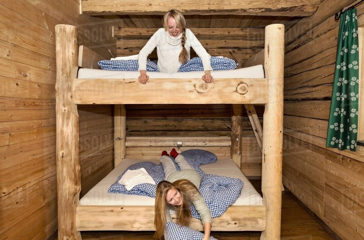Picture of: Two Young Women Friends Fooling Around On Bunk Beds In Log Cabin Stock Photo Dissolve