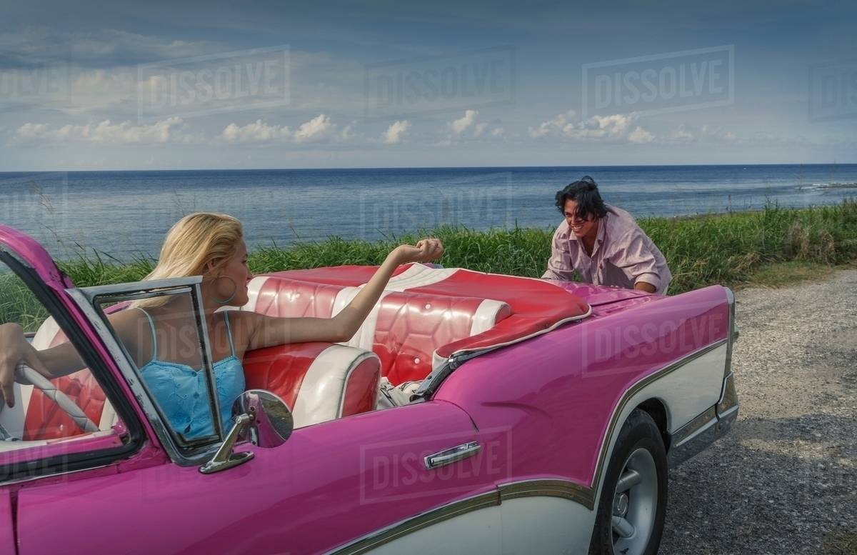 Young Man Pushing Pink Vintage Convertible At Coast Whilst Girlfriend Drives Havana Cuba Stock Photo Dissolve