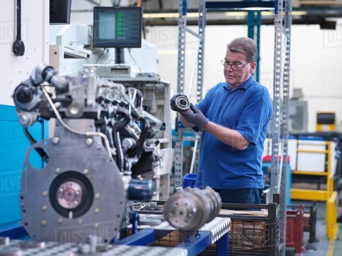 engineer with gear wheel and diesel engine in engineering factory