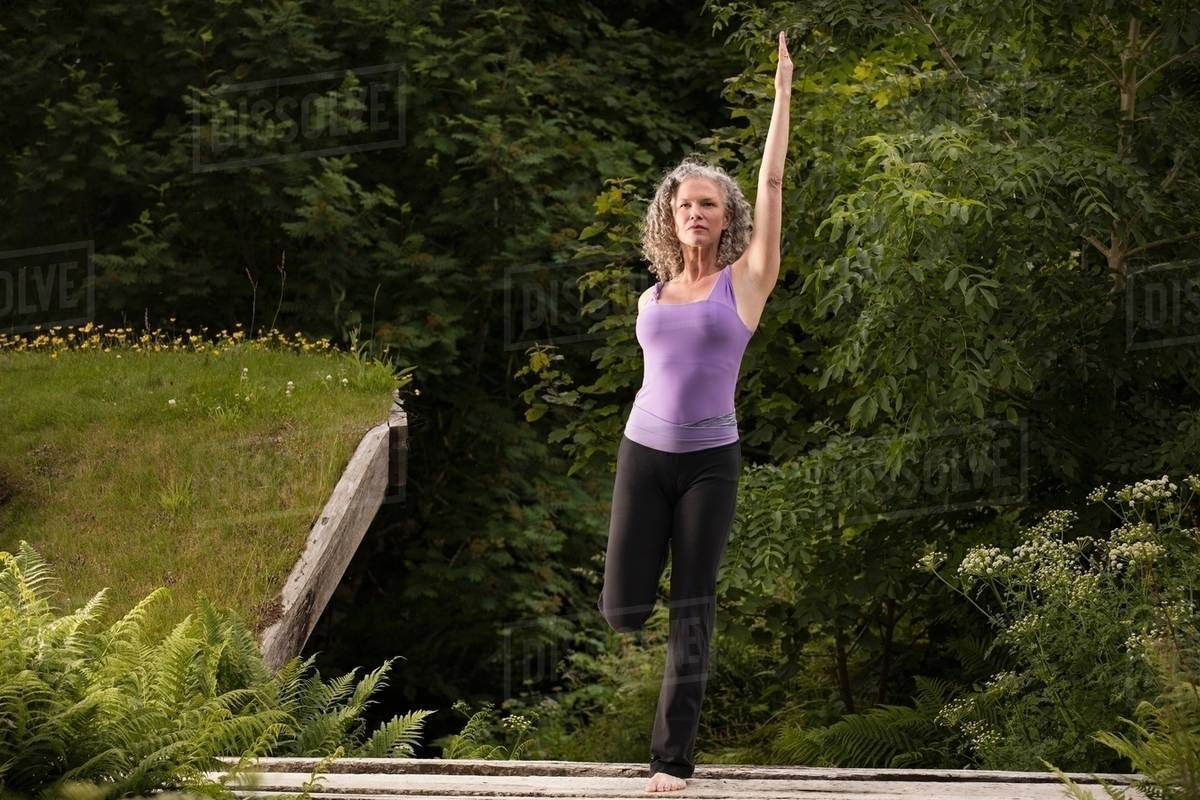 Mature Woman Practicing Yoga Pose On One Leg In Garden