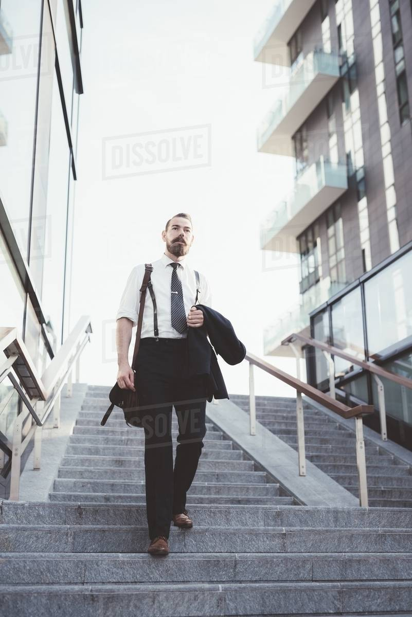 Businessman carrying jacket moving down city stairway Royalty-free stock photo