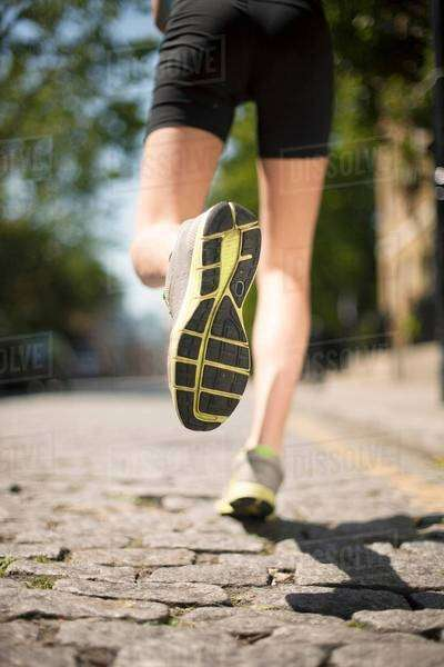 Runner jogging on cobbled street Royalty-free stock photo
