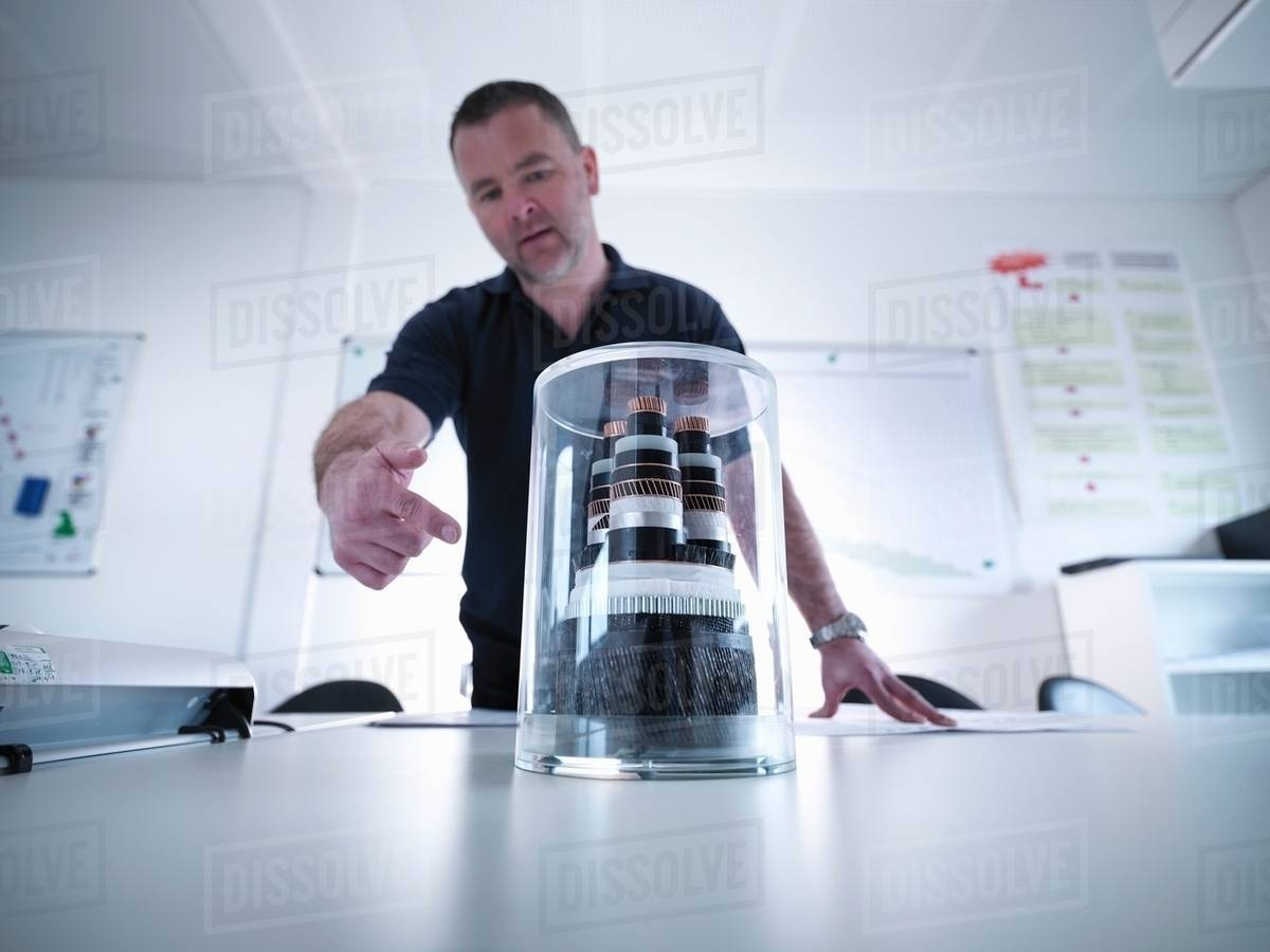 Offshore windfarm engineer discussing power cable sample in conference room  stock photo