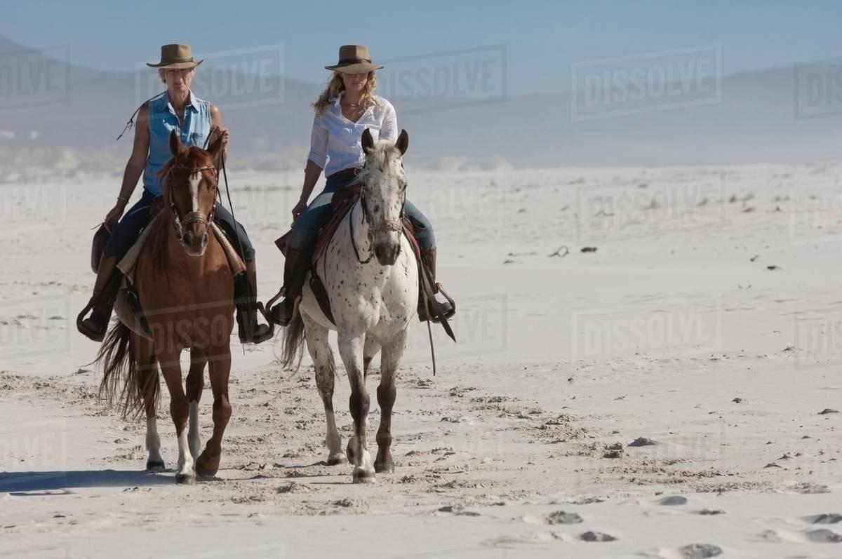 2 People Riding Horses On The Beach Stock Photo Dissolve