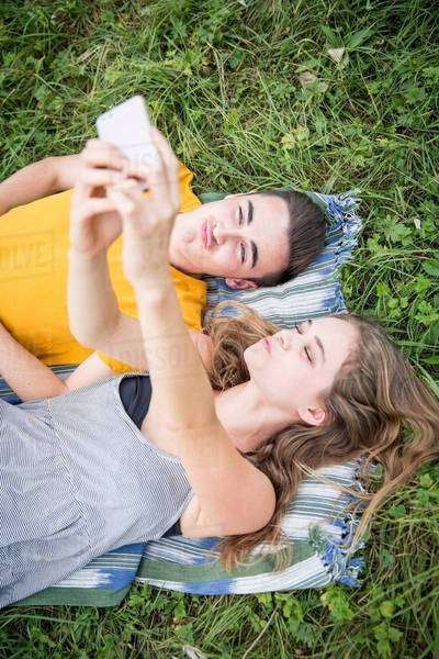 Young couple lying on grass in field, taking self portrait using smartphone Royalty-free stock photo