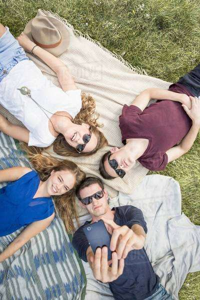 Group of young adults lying on picnic blankets, taking self portrait using smartphone Royalty-free stock photo