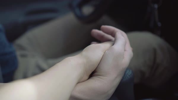 A man and woman holding hands while driving in a vehicle. Royalty-free stock video