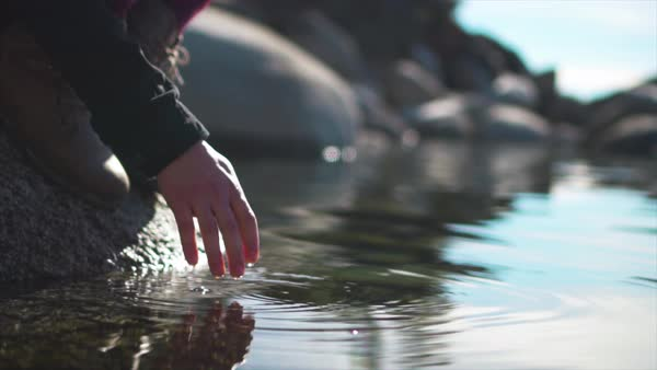 A slow motion shot of a woman's hand gracefully touching the water in a mountain lake as it drips between her fingers Royalty-free stock video