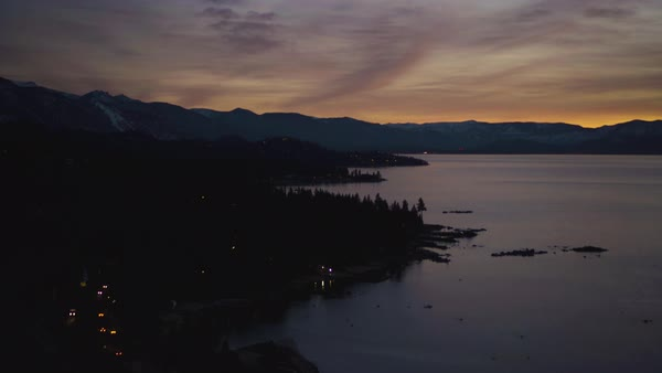 Panning shot of a beautiful sunset over a mountain lake while cars drive on the road below. Royalty-free stock video