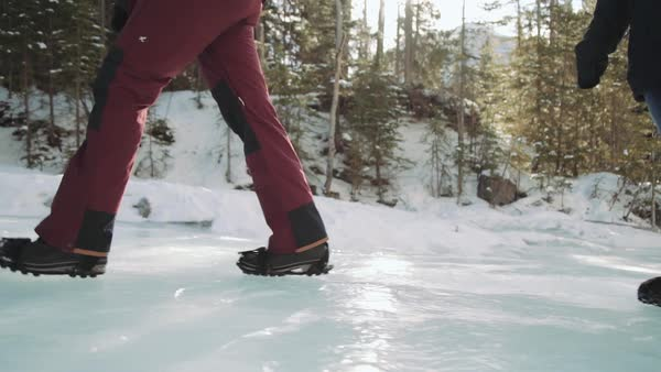 Medium shot of people walking on a frozen creek in Grotto Canyon Royalty-free stock video