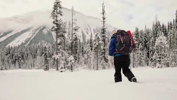 Wide-angle shot of a person hiking in snowy clearing Royalty-free stock video