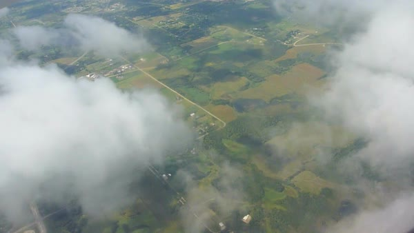 Flying in airplane through clouds over farmland Royalty-free stock video