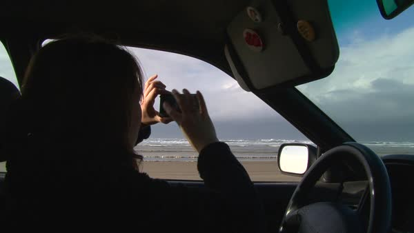 Woman in car with camera phone takes photo of the ocean. Royalty-free stock video