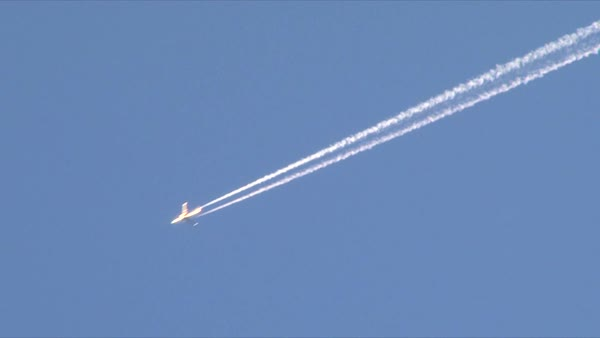 Airplane flies overhead on clear, blue sky day leaving behind vapor trail jet contrails. Royalty-free stock video