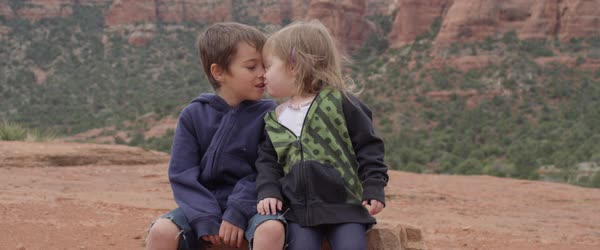 Two boys kissing their little sibling girls face together in a small boy and a little girl share a kiss as they sit on a rock on thecheapjerseys Gallery