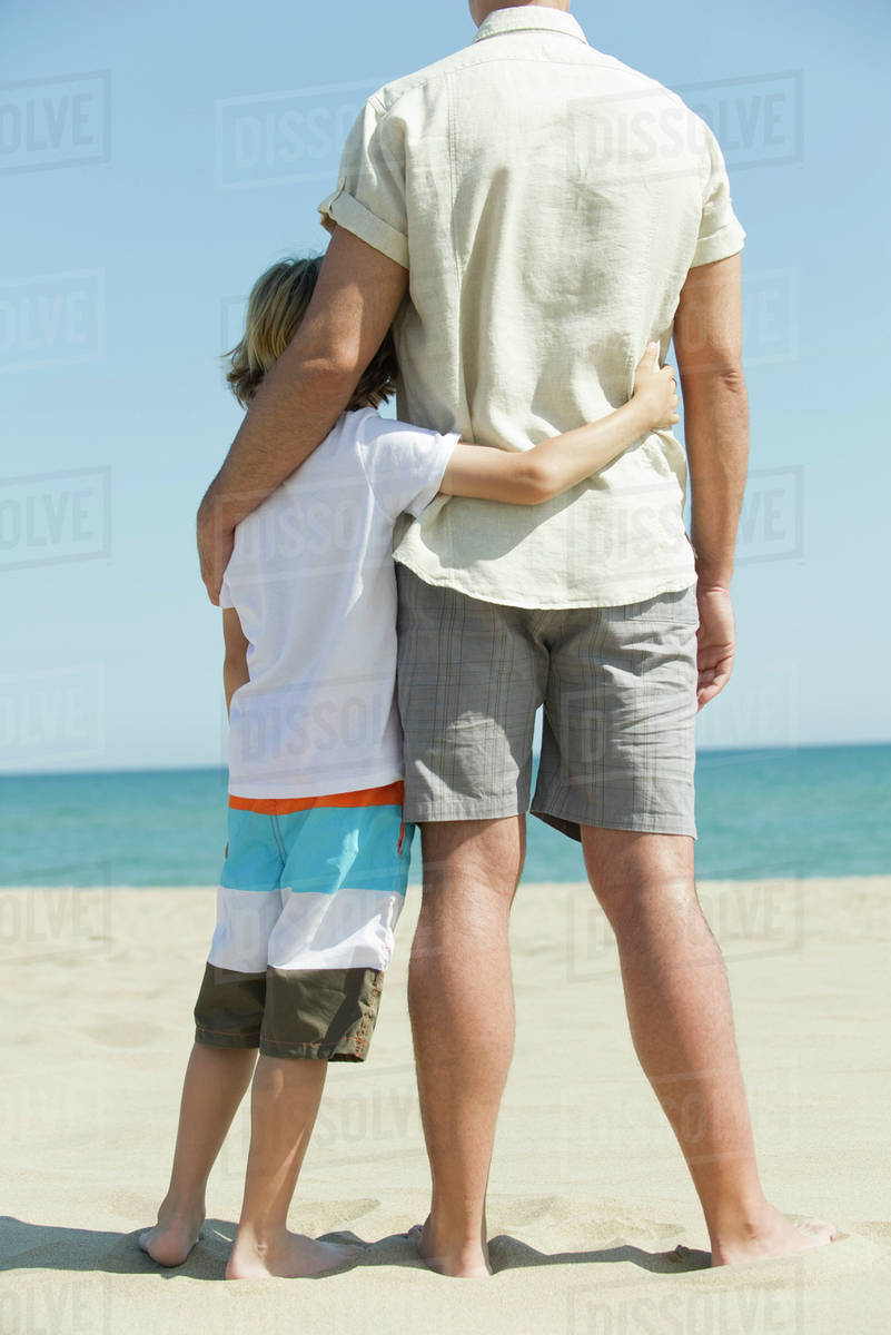 fa4d882f2 Father and young son standing together at the beach, rear view ...