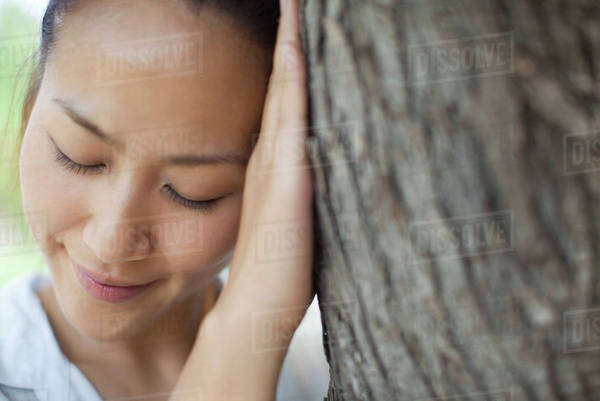 704e96d202ded1 Woman resting head against tree trunk with eyes closed Royalty-free stock  photo
