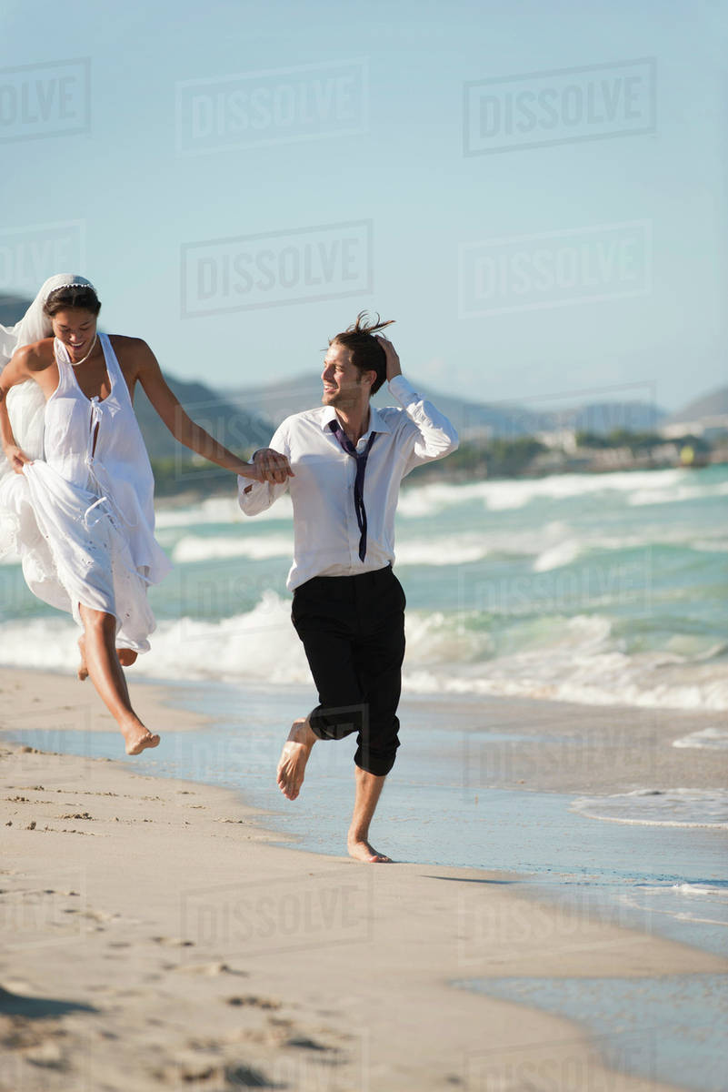 Incredible Bride And Groom Running Hand And Hand At The Beach Stock Photo Download Free Architecture Designs Scobabritishbridgeorg