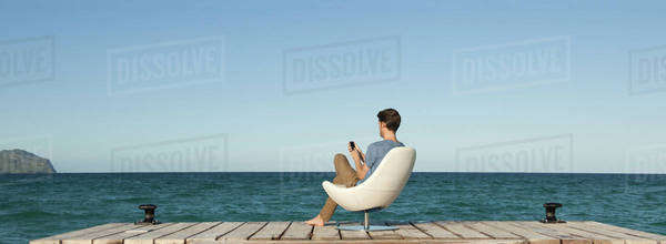 Man siitng in chair on dock using cell phone, rear view Royalty-free stock photo