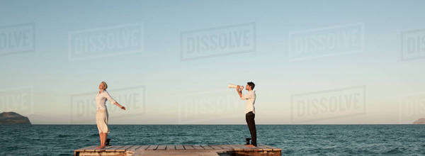 Couple standing on pier, man talking to woman through megaphone Royalty-free stock photo