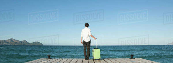 Man standing on dock with suitcase, looking at ocean view, rear view Royalty-free stock photo