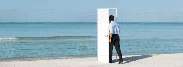 Man walking into open door on beach, rear view Royalty-free stock photo