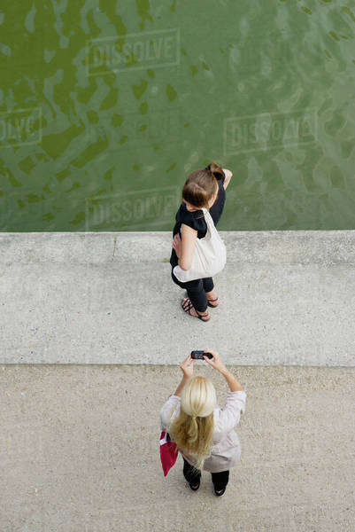 Young woman photographing friend with cell phone, elevated view Royalty-free stock photo
