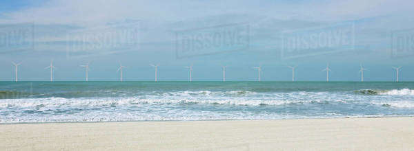 Wind turbines along horizon in ocean Royalty-free stock photo