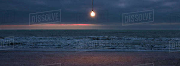 Light bulb illuminated over beach at sunset Royalty-free stock photo