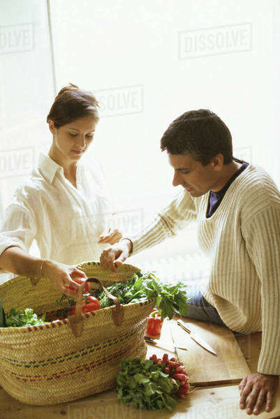 Couple removing fresh produce from basket Royalty-free stock photo