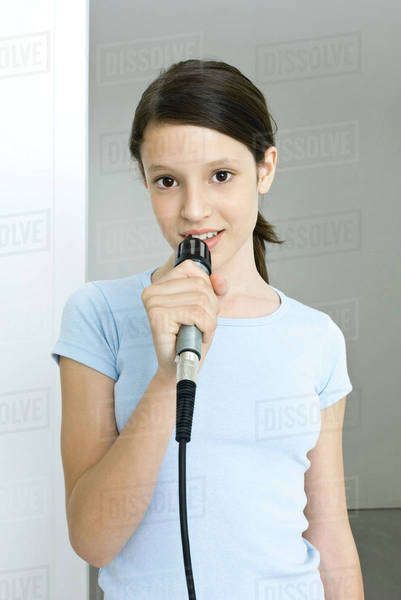 Preteen girl singing into microphone, smiling at camera Royalty-free stock photo