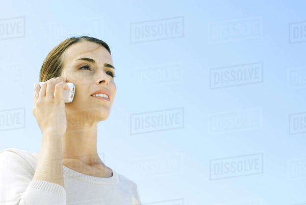 Woman using cell phone outdoors, looking away, low angle view Royalty-free stock photo
