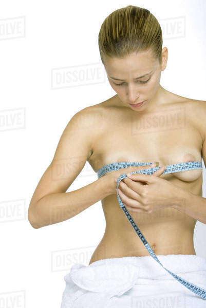 Nude woman measuring breasts with measuring tape, looking down Royalty-free stock photo